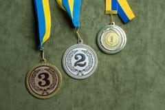Oro, plata o medalla de bronce con las cintas amarillas y azules imagen de archivo
