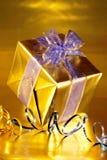 Oro presente con i nastri blu Fotografia Stock Libera da Diritti