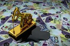Oro Pumpjack y aceite derramado en el dirham de United Arab Emirates Imagen de archivo libre de regalías