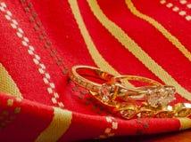 Oro su oro--Anelli e braccialetto intrecciati Immagine Stock