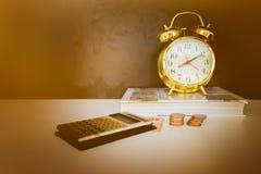Oro viejo del vintage del dinero, de la calculadora y del despertador sobre el fondo blanco y negro con el espacio de la copia añ Fotografía de archivo libre de regalías