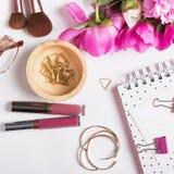 Oro y accesorios y peonías femeninos del rosa en la parte posterior del blanco Fotos de archivo