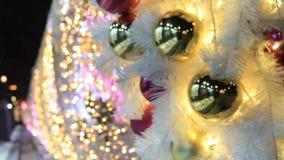 Oro y bolas y guirnalda brillantes rojas en árbol de abeto blanco Fondo Defocused almacen de video