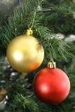 Oro y ornamentos rojos que cuelgan en árbol Imagen de archivo
