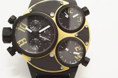Oro y reloj del negro Fotografía de archivo
