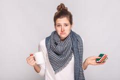 Oroa den förbryllade kvinnainnehavkoppen med te, många preventivpillerar Sh studio arkivbilder