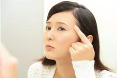 Oroad kvinna som har hudproblem arkivfoto
