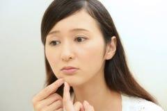 Oroad kvinna som har hudproblem royaltyfri fotografi