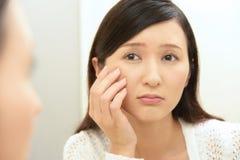 Oroad kvinna som har hudproblem royaltyfri bild