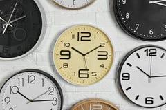 Orologi analogici differenti che appendono sulla parete bianca fotografie stock libere da diritti