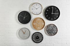 Orologi analogici differenti che appendono sulla parete bianca immagini stock libere da diritti