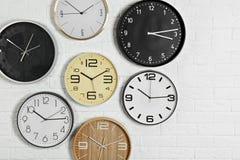 Orologi analogici differenti che appendono sulla parete bianca fotografia stock libera da diritti