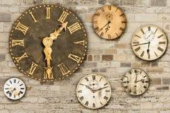 Orologi d'annata che appendono su un vecchio muro di mattoni Fotografie Stock