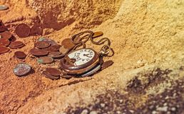 Orologi da tasca tagliati d'annata e vecchie monete su una scogliera Immagine Stock