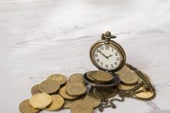 Orologi dell'annata sulle monete, sul tempo e sui soldi Fotografia Stock