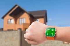 Orologi di Smart con sicurezza domestica app su una mano sui precedenti della costruzione Fotografie Stock Libere da Diritti