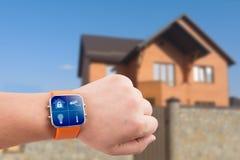 Orologi di Smart con sicurezza domestica app su una mano sui precedenti della costruzione Immagini Stock Libere da Diritti