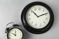 Orologi differenti su fondo leggero Cambiamento di tempo immagine stock libera da diritti