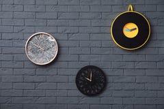 Orologi differenti sul muro di mattoni fotografie stock