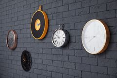 Orologi differenti sul muro di mattoni fotografia stock