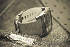 Orologi e cinghia di cuoio e del jeans Fotografia Stock