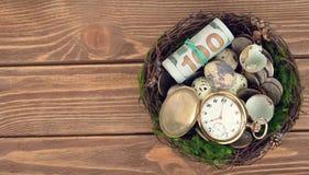 Orologi, soldi ed uova in un nido Immagine Stock