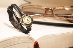 Orologi su fondo del libro Immagini Stock Libere da Diritti