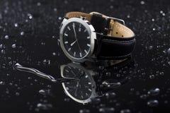 Orologi su un acrilico scuro del fondo fotografia stock