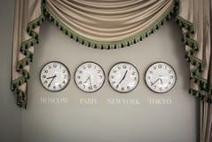 Orologi su una parete con la fascia oraria di paese differente fotografie stock