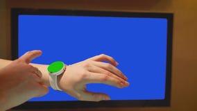 Orologi verdi dello schermo dei colpi della ragazza Schermo blu del set televisivo su fondo stock footage