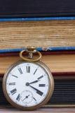 Orologio antico sul fondo dei libri Fotografia Stock