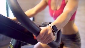 Orologio astuto che mostra una frequenza cardiaca di esercitazione della donna nella palestra stock footage