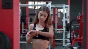Orologio astuto giallo che mostra una frequenza cardiaca di esercitazione della giovane donna nella palestra stock footage