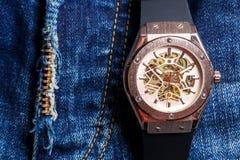 Orologio automatico degli uomini con il meccanismo visibile sul backgro delle blue jeans Immagine Stock Libera da Diritti