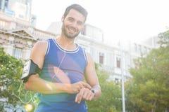 Orologio bello sorridente di frequenza cardiaca della regolazione dell'atleta Immagini Stock
