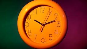 Orologio bianco su fondo variopinto Movimento lento archivi video