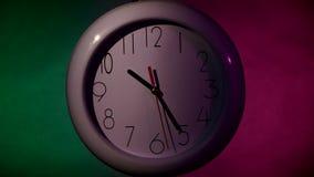 Orologio bianco sulla parete di legno della plancia di colore, notte stock footage