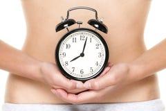 Orologio biologico che ticchetta - orologio della tenuta della donna Fotografie Stock Libere da Diritti