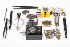 Orologio che ripara gli strumenti su bianco Fotografia Stock