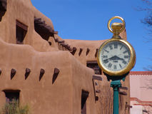 Orologio con l'edificio del Adobe a Santa Fe Fotografia Stock