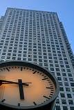 Orologio con l'edificio per uffici d'acciaio molto alto Fotografie Stock