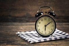 Orologio d'annata del nero dell'allarme sulla tavola scozzese blu dei vestiti Fotografia Stock Libera da Diritti