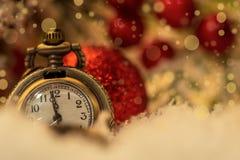 Orologio d'annata e coni del nuovo anno coperti di neve fotografie stock