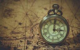 Orologio d'annata sulla mappa di vecchio mondo immagini stock libere da diritti