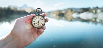 Orologio d'annata tenuto in mano, vista del autumwn con il lago ed alberi nei precedenti fotografia stock