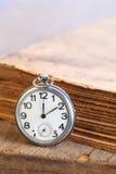 Orologio da tasca accanto al libro Immagine Stock