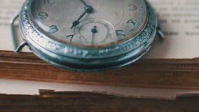 Orologio da tasca antico d'annata sui precedenti di vecchi libri stock footage