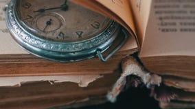 Orologio da tasca antico d'annata sui precedenti di vecchi libri video d archivio