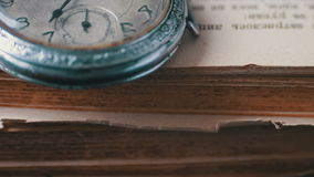 Orologio da tasca antico d'annata sui precedenti di vecchi libri archivi video