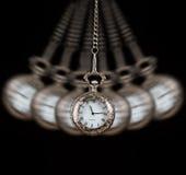 Orologio da tasca che oscilla su un fondo nero a catena Immagini Stock
